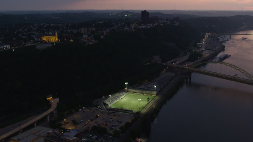 4K stock footage aerial video flying over Highmark Stadium toward St. Mary of the Mount, Pittsburgh, Pennsylvania, twilight Aerial Stock Footage | AX108_102
