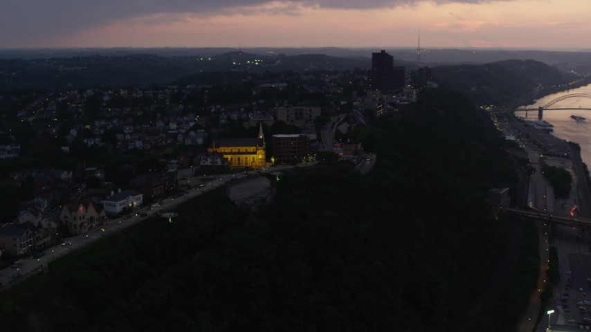 4K stock footage aerial video of St. Mary of the Mount Church and suburban neighborhoods, Pittsburgh, Pennsylvania, twilight Aerial Stock Footage | AX108_103