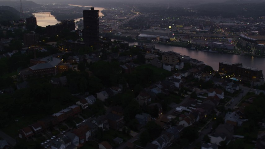 4K stock footage aerial video flying over suburban neighborhoods and office buildings above Ohio River, Pittsburgh, Pennsylvania, twilight Aerial Stock Footage   AX108_105