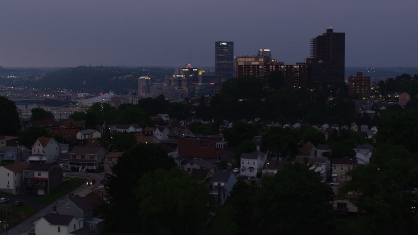4K stock footage aerial video flying over hilltop neighborhoods toward Downtown Pittsburgh skyline, Pennsylvania, twilight Aerial Stock Footage | AX108_109