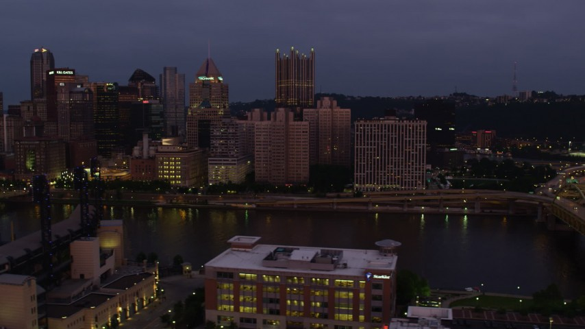 4K stock footage aerial video flying by Downtown Pittsburgh skyscrapers from Fort Duquesne Bridge, Pennsylvania, twilight Aerial Stock Footage | AX108_121