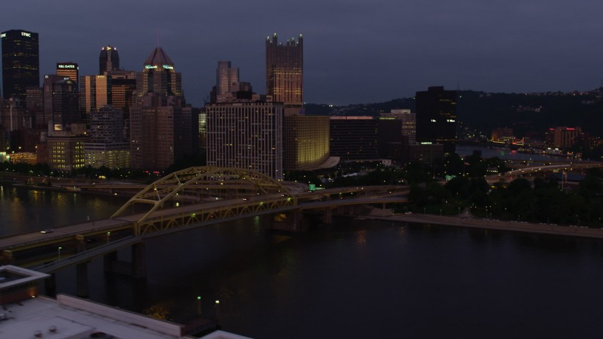 4K stock footage aerial video flying by Downtown Pittsburgh skyscrapers revealing Point State Park, Pennsylvania, twilight Aerial Stock Footage | AX108_122