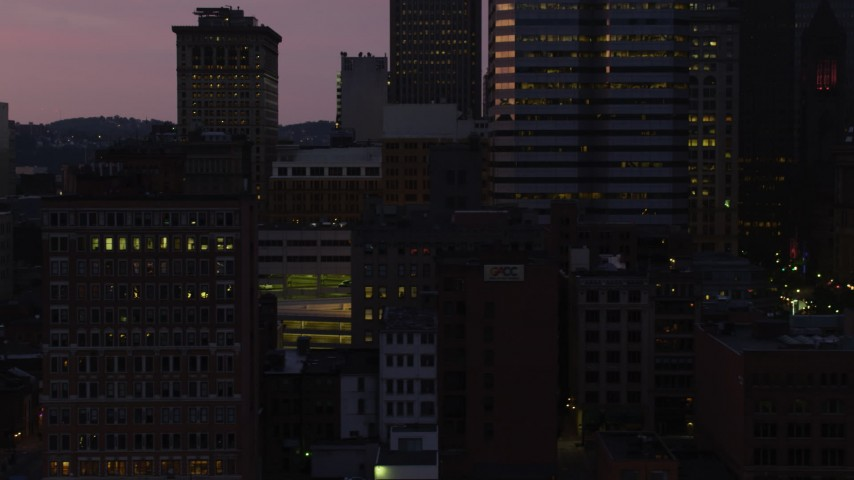 4K stock footage aerial video flying by skyscrapers and city streets, Downtown Pittsburgh, Pennsylvania, twilight Aerial Stock Footage | AX108_129