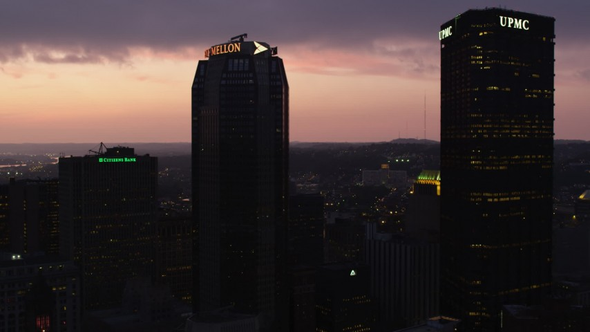4K stock footage aerial video flying by BNY Mellon Center and U.S. Steel Tower, Downtown Pittsburgh, twilight Aerial Stock Footage | AX108_133