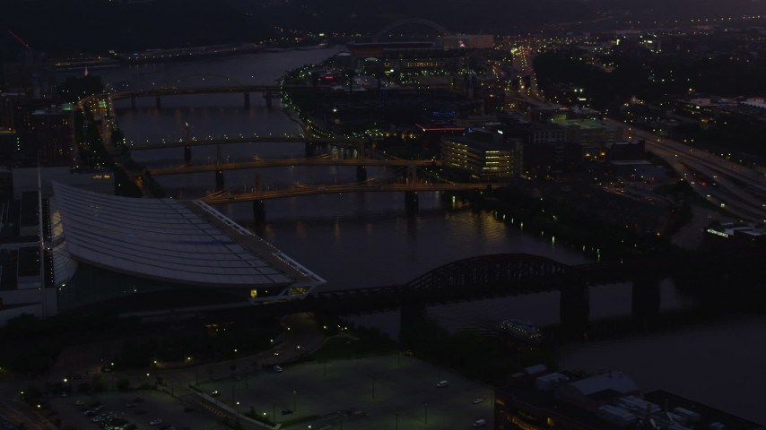 4K stock footage aerial video flying by bridges spanning the Allegheny River and PNC Park, Pittsburgh, twilight Aerial Stock Footage | AX108_136