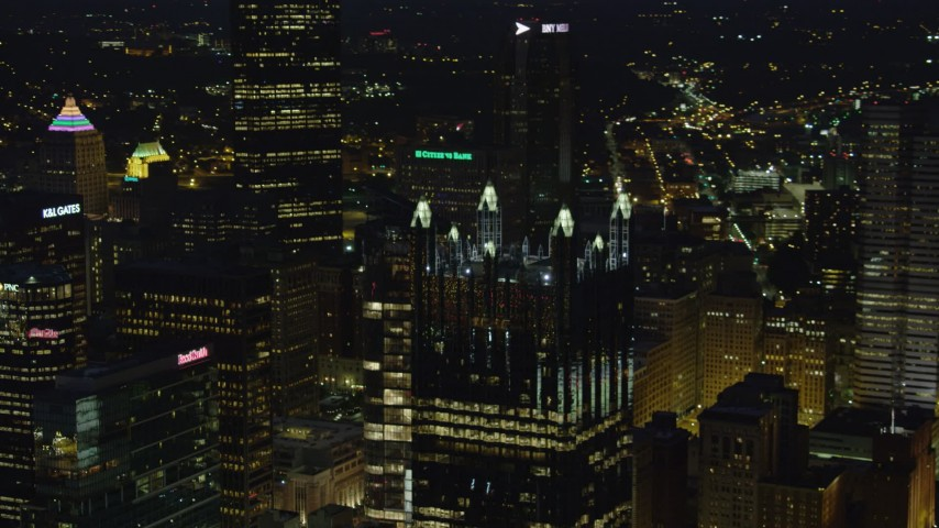 4K stock footage aerial video flying by PPG Place revealing tops of skyscrapers, Pittsburgh, night Aerial Stock Footage | AX108_212