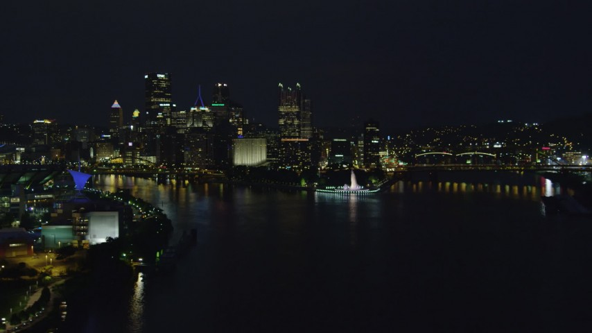 4K stock footage aerial video descending toward river by Point State Park, Downtown Pittsburgh, night Aerial Stock Footage | AX108_217