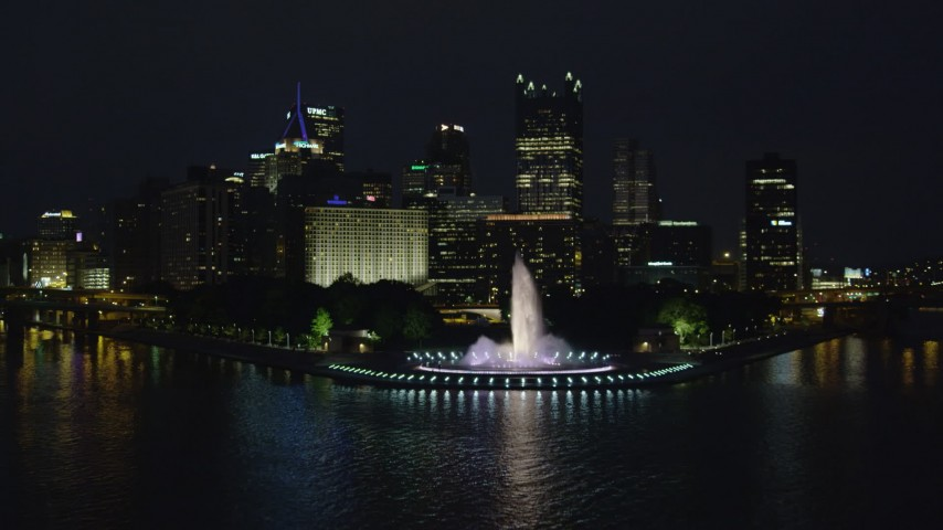 4K stock footage aerial video flying over Point State Park toward skyscrapers, Downtown Pittsburgh, night Aerial Stock Footage | AX108_219