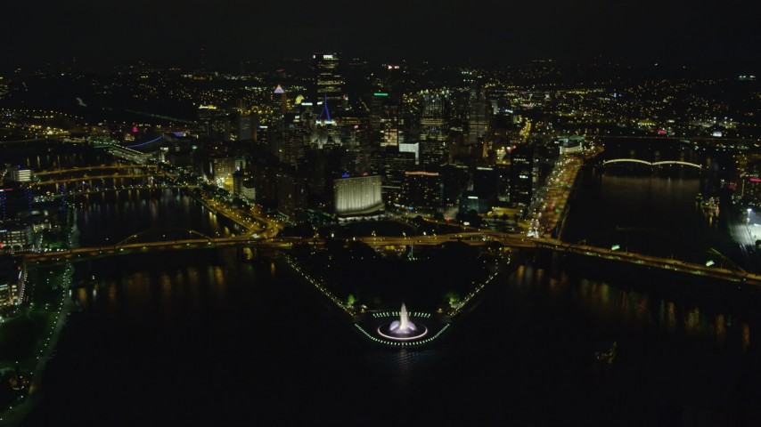 4K stock footage aerial video flying over Point State Park Fountain toward Downtown Pittsburgh, Pennsylvania, night Aerial Stock Footage | AX108_235