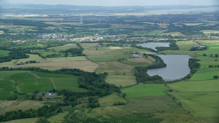 6K stock footage aerial video of green farms and a reservoir, Denny, Scotland Aerial Stock Footage | AX109_004