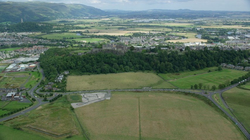 6K stock footage aerial video of a reverse view of Stirling Castle, neighborhoods, and farmland, Scotland Aerial Stock Footage   AX109_018