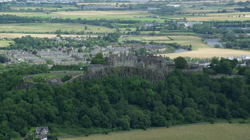 6K stock footage aerial video of hilltop Stirling Castle among trees, Scotland Aerial Stock Footage | AX109_019