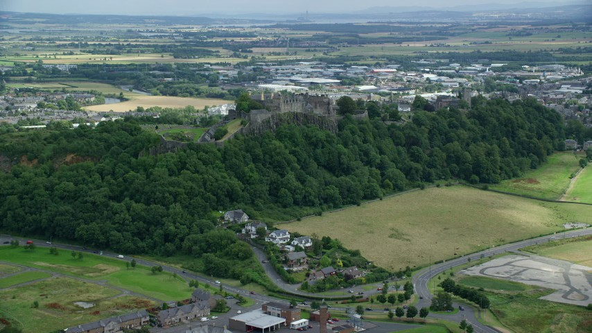 6K stock footage aerial video approach Stirling Castle among tree covered hillside, Scotland Aerial Stock Footage | AX109_022