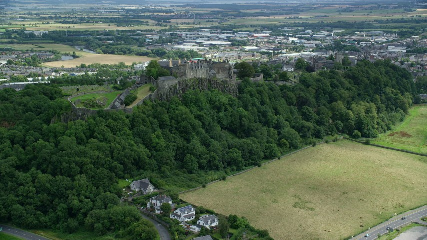 6K stock footage aerial video of an approach to Stirling Castle on a tree covered hillside, Scotland Aerial Stock Footage | AX109_023