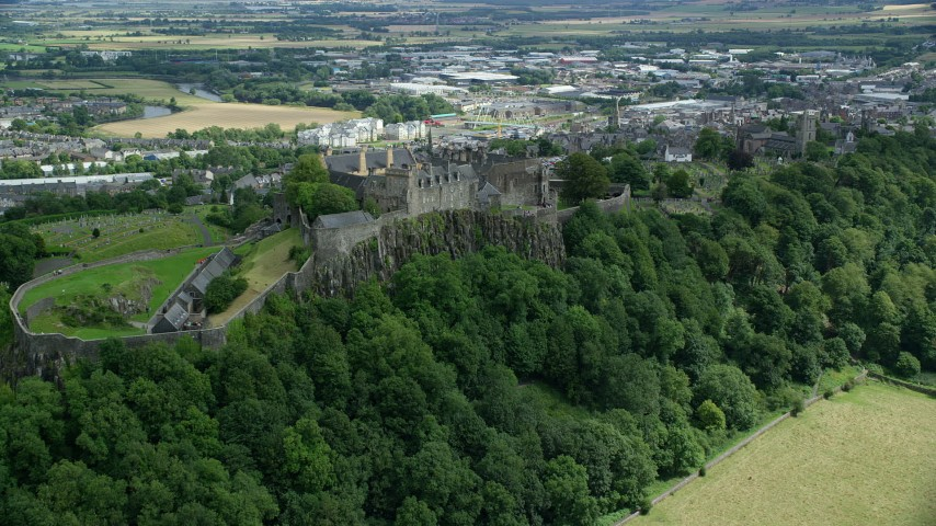 6K stock footage aerial video of flying toward Stirling Castle on a tree covered hill, Scotland Aerial Stock Footage | AX109_024