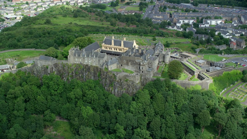6K stock footage aerial video of passing Stirling Castle atop a tree covered hill, Scotland Aerial Stock Footage | AX109_038