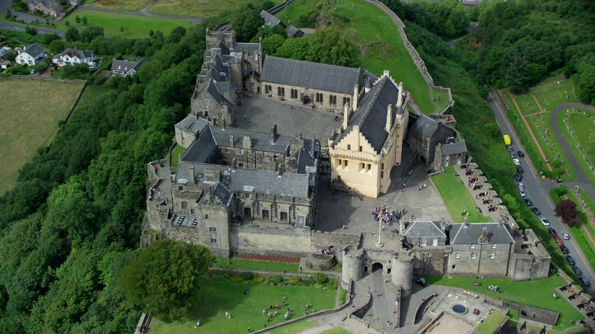 6K stock footage aerial video orbiting historic Stirling Castle with tourists, Scotland Aerial Stock Footage | AX109_040