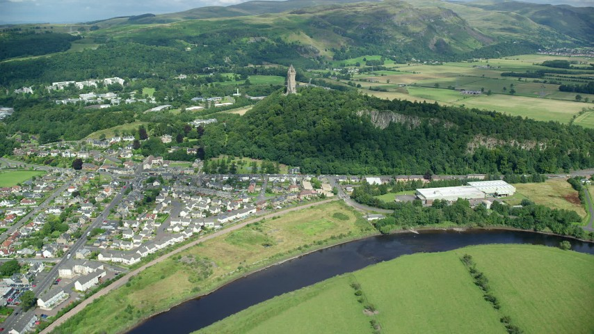6K stock footage aerial video of approaching Wallace Monument surrounded by trees, Stirling, Scotland Aerial Stock Footage | AX109_046