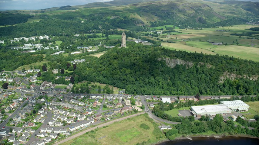 6K stock footage aerial video of approaching the historic Wallace Monument surrounded by trees, Stirling, Scotland Aerial Stock Footage | AX109_047