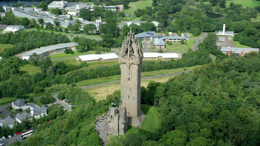 6K stock footage aerial video of orbiting historic Wallace Monument with tree coverage, Stirling, Scotland Aerial Stock Footage | AX109_049