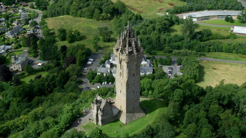 6K stock footage aerial video of orbiting iconic Wallace Monument looking down on residential area, Stirling, Scotland Aerial Stock Footage | AX109_050