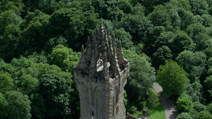 6K stock footage aerial video of orbiting top of historic Wallace Monument among trees, Stirling, Scotland Aerial Stock Footage | AX109_052