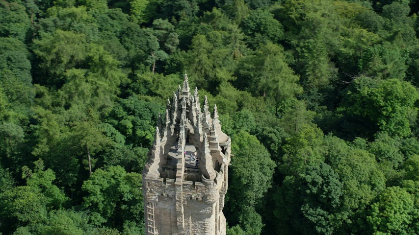 6K stock footage aerial video of orbiting top of iconic Wallace Monument surrounded in trees, Stirling, Scotland Aerial Stock Footage | AX109_053