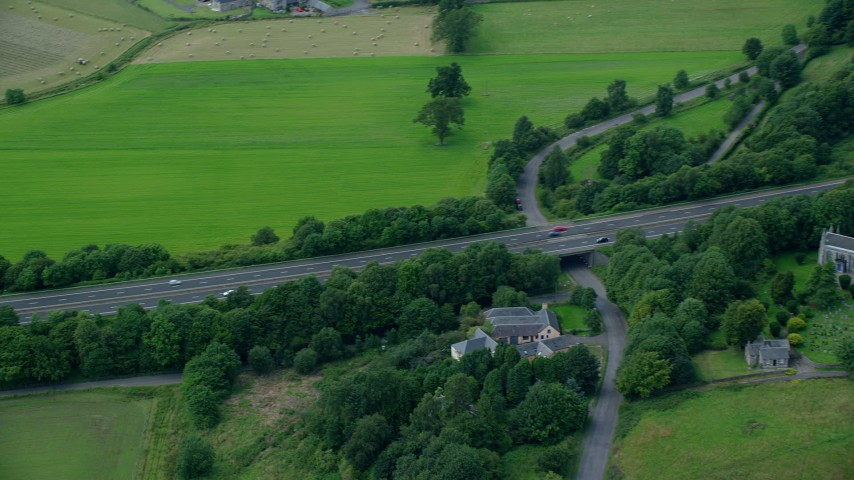 6K stock footage aerial video of M9 Highway lined with trees, Stirling, Scotland Aerial Stock Footage | AX109_058