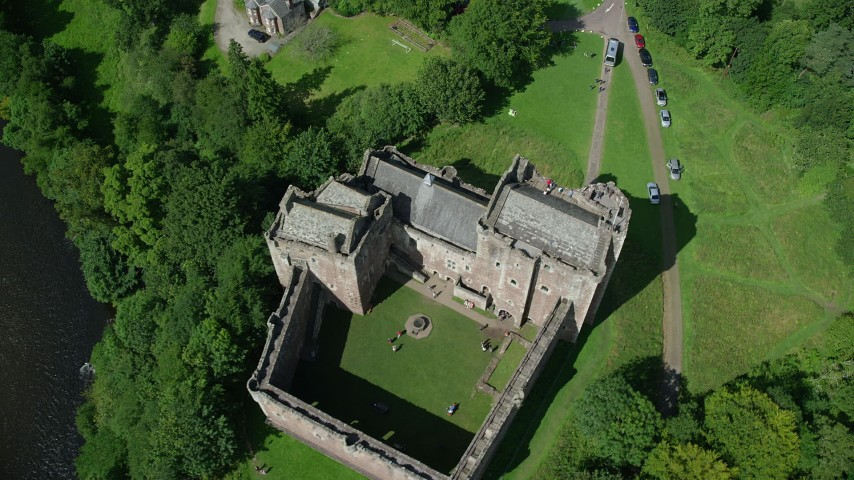 6K stock footage aerial video of tilting to a bird's eye view of historic Doune Castle and its grounds, Scotland Aerial Stock Footage | AX109_072