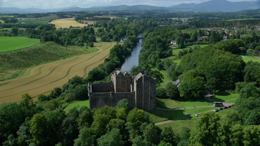 6K stock footage aerial video fly over Doune Castle and River Teith line with trees, Scotland Aerial Stock Footage | AX109_076