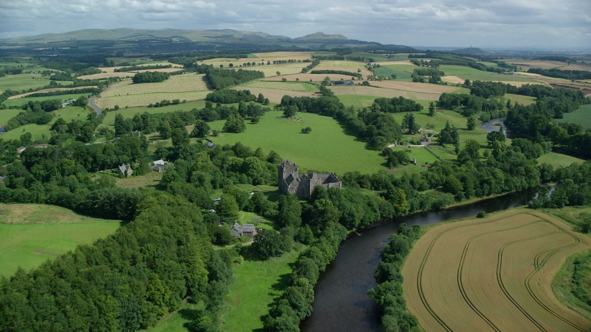 6K stock footage aerial video of flying over historic Doune Castle toward farmland, Scotland Aerial Stock Footage | AX109_087