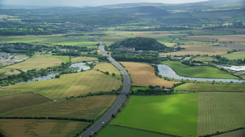 6K stock footage aerial video of M9 highway and farmland, Stirling, Scotland Aerial Stock Footage | AX109_095