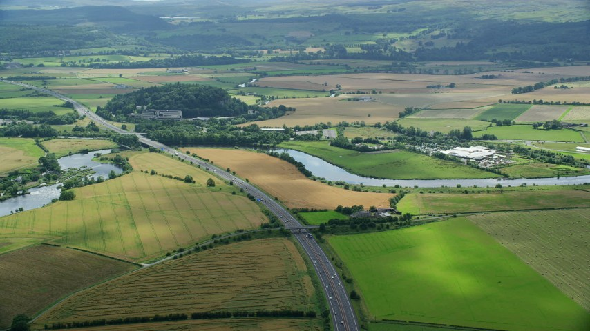 6K stock footage aerial video of M9 highway and farmland in Stirling, Scotland Aerial Stock Footage | AX109_096