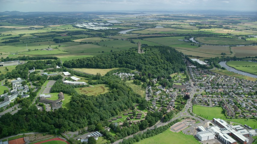 6K stock footage aerial video approach Wallace Monument surrounded by trees in Stirling, Scotland Aerial Stock Footage | AX109_098