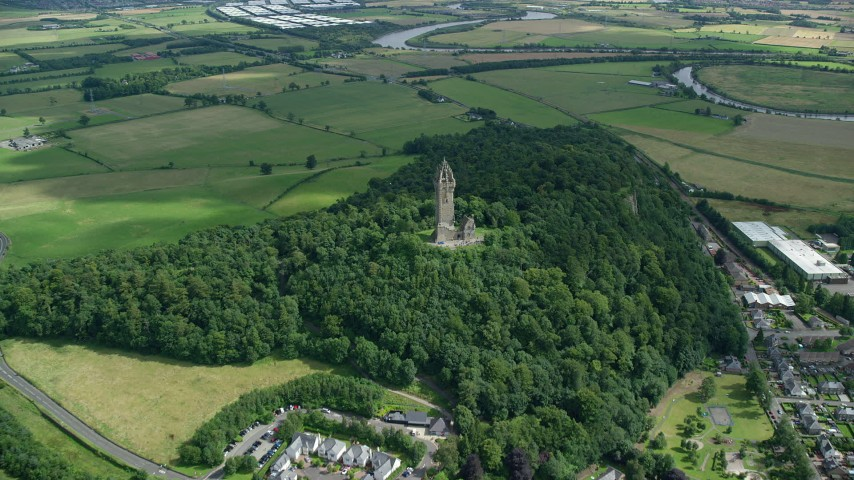 6K stock footage aerial video of approaching Wallace Monument surrounded by trees, Stirling, Scotland Aerial Stock Footage | AX109_099