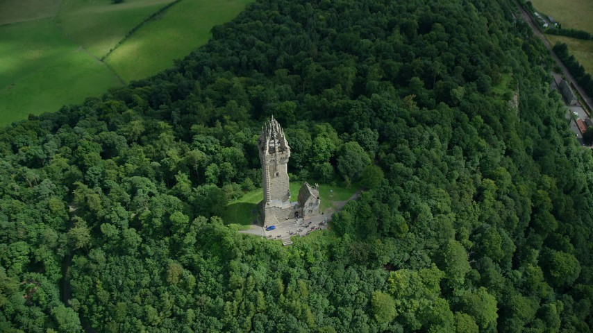 6K stock footage aerial video of historic Wallace Monument surrounded by trees, Scotland Aerial Stock Footage | AX109_100