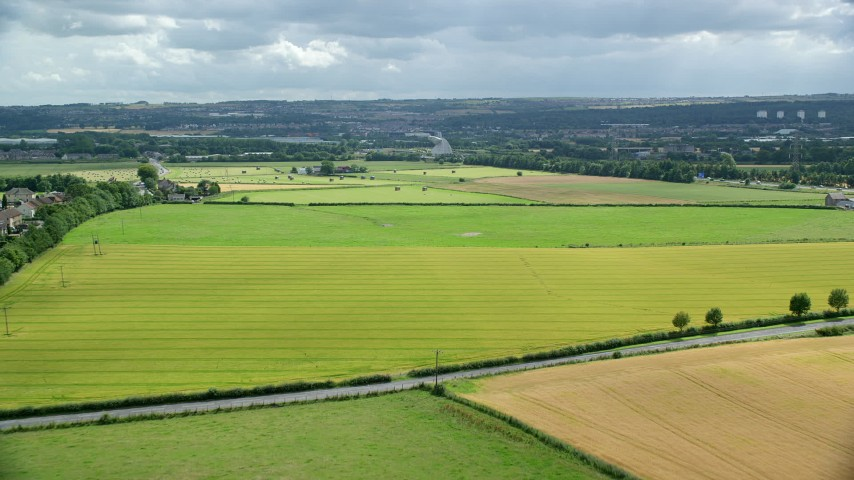 6K stock footage aerial video of green Scottish farm fields seen while approaching The Kelpies, Falkirk, Scotland Aerial Stock Footage | AX109_118