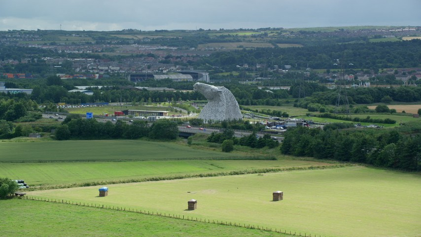 6K stock footage aerial video approach The Kelpies sculptures from fields, Falkirk, Scotland Aerial Stock Footage | AX109_120