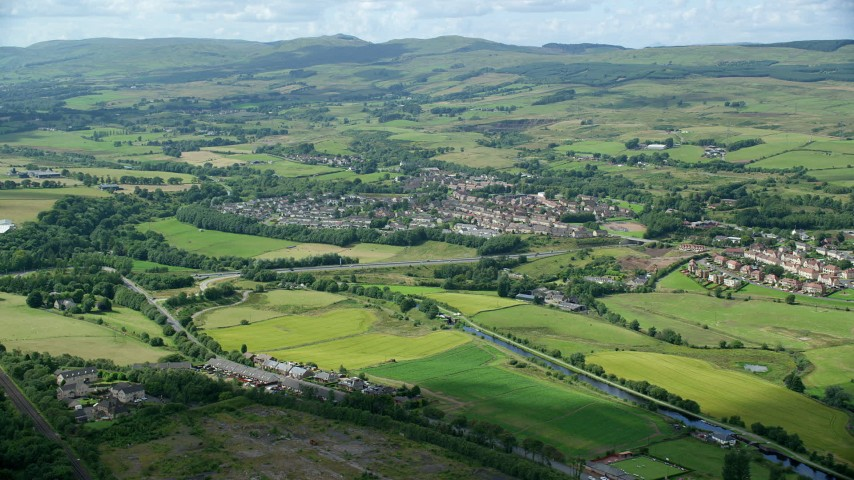 6K stock footage aerial video of Scottish farm fields and village homes in Bonnybridge, Scotland Aerial Stock Footage | AX109_170