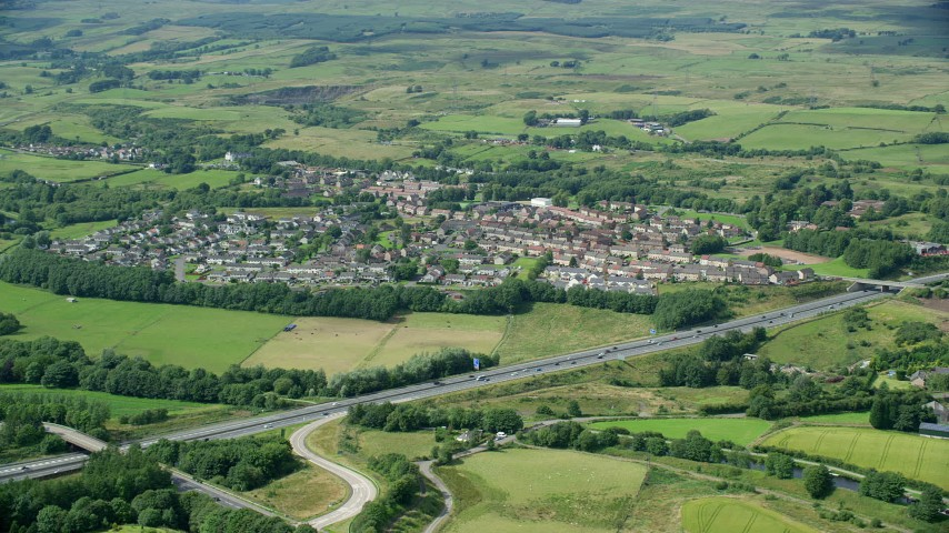 6K stock footage aerial video of farm fields and highway M80 by rural village homes, Bonnybridge, Scotland Aerial Stock Footage | AX109_172