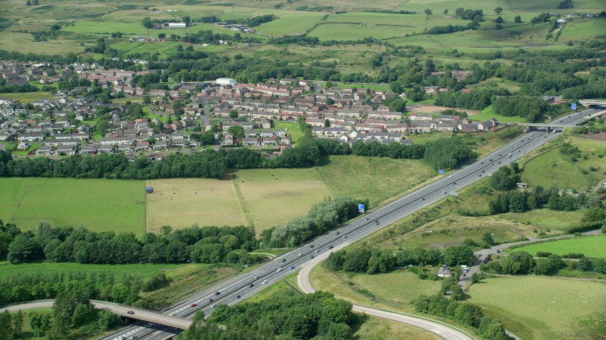 6K stock footage aerial video of highway M80 and rural village homes by farm fields, Bonnybridge, Scotland Aerial Stock Footage | AX109_173