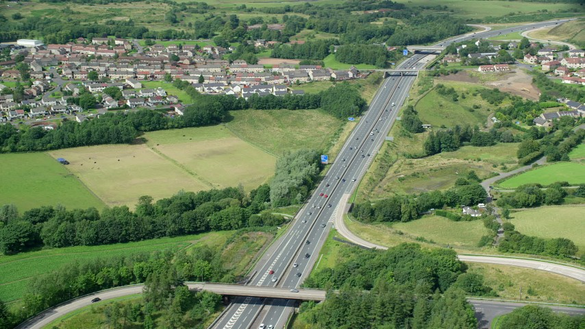 6K stock footage aerial video of orbiting highway M80 by farmland and Scottish village, Bonnybridge, Scotland Aerial Stock Footage | AX109_174