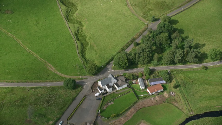 6K stock footage aerial video tilt to bird's eye of a farm with green fields in Denny, Scotland Aerial Stock Footage AX110_010 | Axiom Images