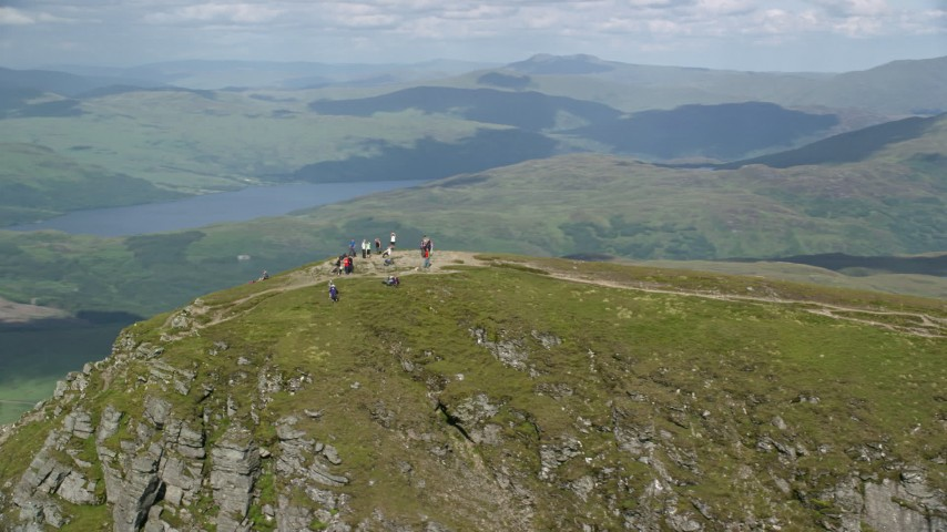 6K stock footage aerial video of flyby hikers on Ben Lomond mountain peak in the Scottish Highlands, Scotland Aerial Stock Footage | AX110_052