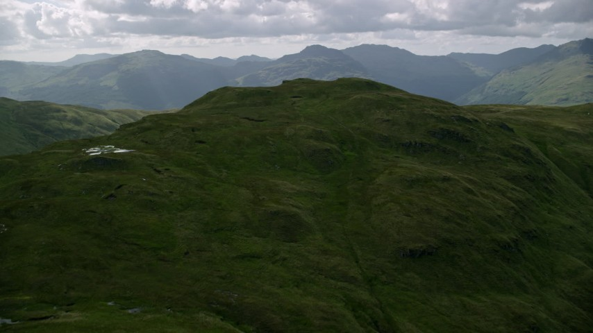 6K stock footage aerial video of approach a green mountain peak, Scottish Highlands, Scotland Aerial Stock Footage | AX110_064