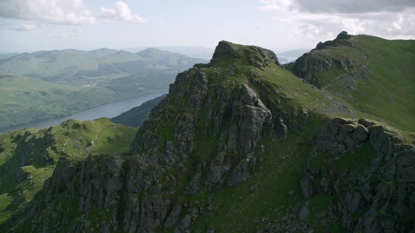 6K stock footage aerial video of flying away from a mountain peak, The Cobbler, Scottish Highlands, Scotland Aerial Stock Footage | AX110_085