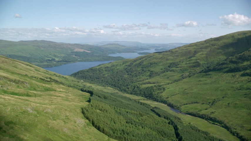6K stock footage aerial video approach blue waters of Loch Lomond from green peaks, Scottish Highlands, Scotland Aerial Stock Footage | AX110_099
