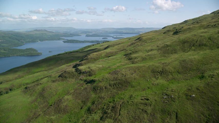 6K stock footage aerial video approach Loch Lomond from lush green mountains, Scottish Highlands, Scotland Aerial Stock Footage | AX110_101