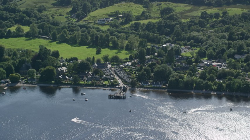 6K stock footage aerial video orbiting a village on the shores of Loch Lomond, Luss, Scottish Highlands Aerial Stock Footage | AX110_107