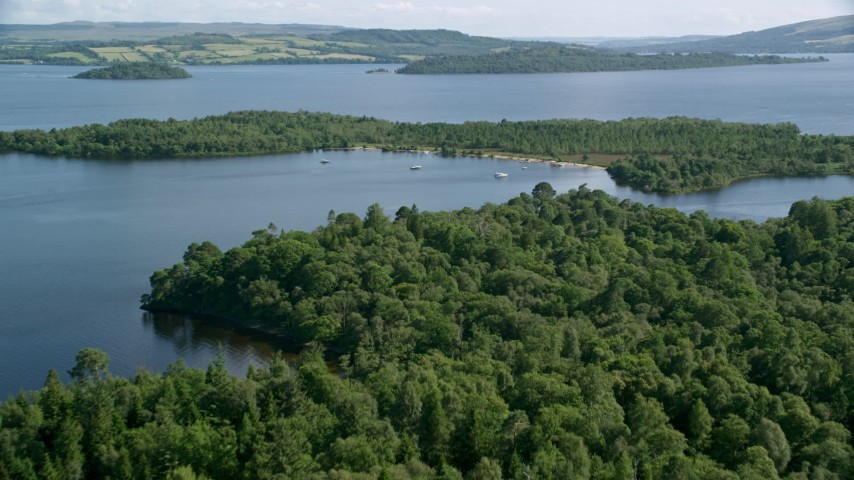 6K stock footage aerial video of fishing boats near a tree-covered island with a narrow beach, Loch Lomond, Scottish Highlands, Scotland Aerial Stock Footage | AX110_108